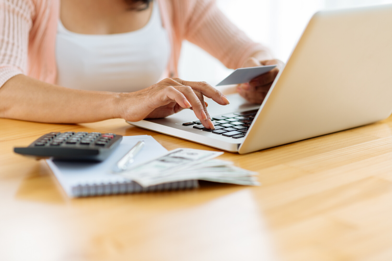 Woman using laptop holding credit card.